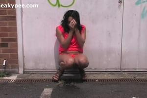 Girl in red dress pisses on the street