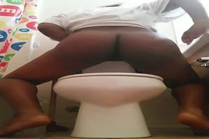 Ebony girl shitting in a toilet